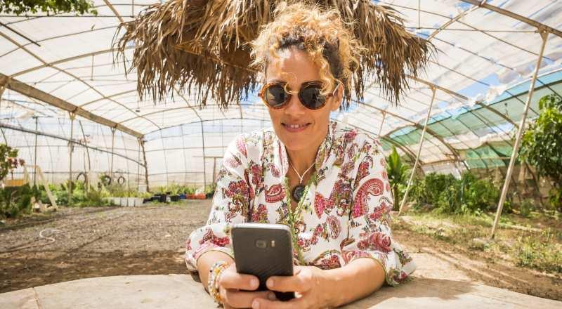 Mulher com celular na mão escolhendo chatbot marketing