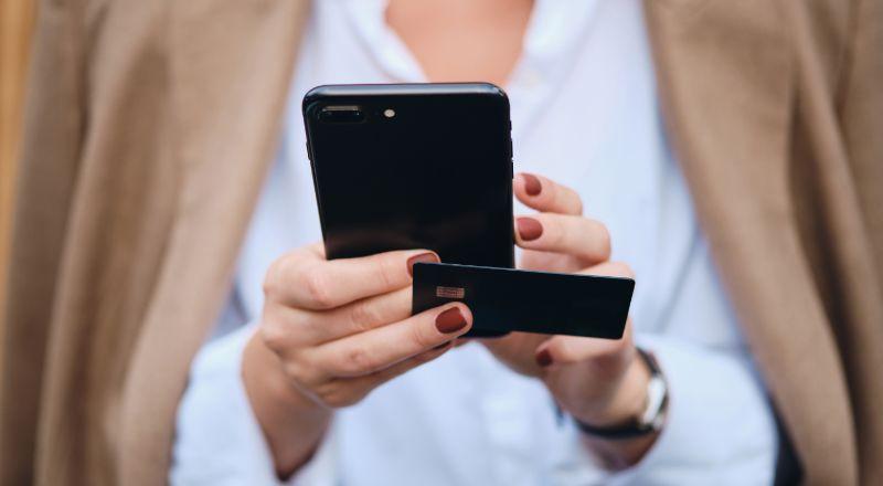 Mãos com celular e cartão para acessar um chatbot SAC