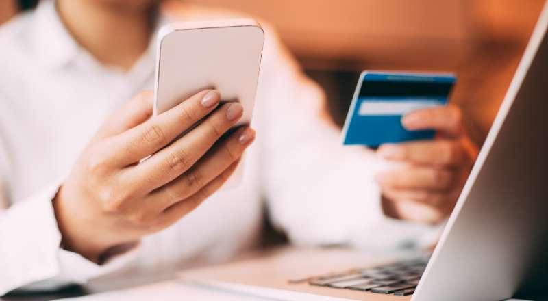 Pessoa com celular e cartão de crédito na mão
