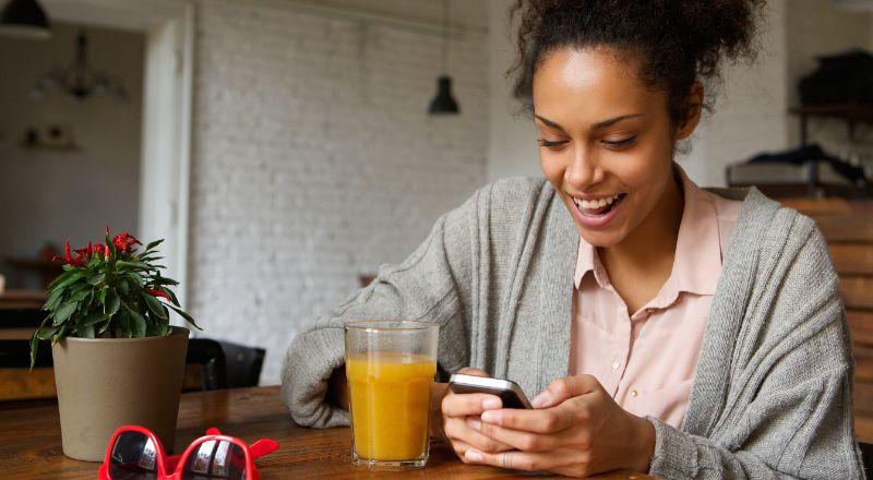 Mulher segura celular e sorri impressionada