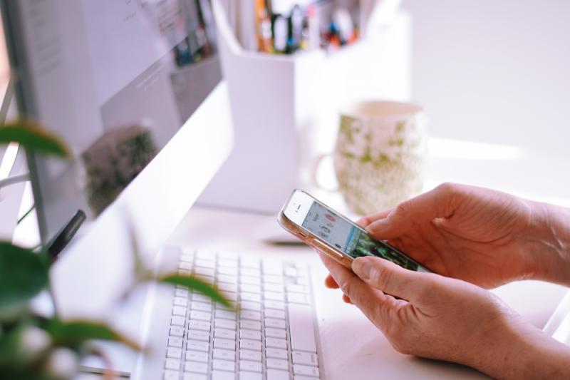 Mão segura celular acessando Chatbot no Instagram