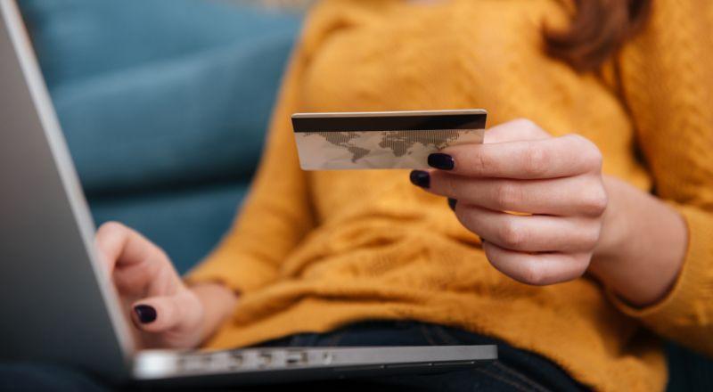 Um mão aparece segurando um cartão de crédito e outra mão mexe no computador